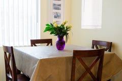 生日束在一个紫色花瓶的黄色玫瑰在一张餐桌上 免版税库存图片