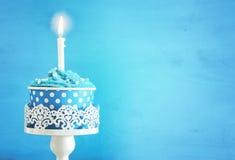 生日概念用杯形蛋糕和一个蜡烛在木桌上 免版税库存图片