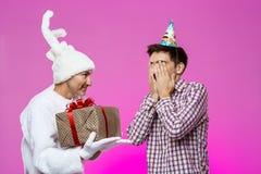 给生日礼物的兔子在紫色背景的醉酒的人 免版税图库摄影
