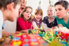 生日聚会吹的蜡烛的孩子在蛋糕 免版税库存图片