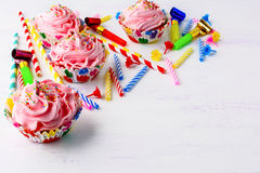 生日聚会邀请用装饰的桃红色杯形蛋糕和cand 免版税库存照片