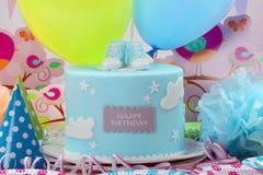 生日蓝色蛋糕和气球在党或招待会 库存照片