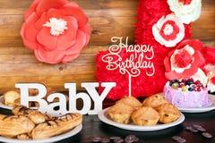 生日蛋糕和松饼与木问候在土气背景签字 木唱歌与信件生日快乐 免版税库存图片