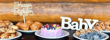生日蛋糕和松饼与木问候在土气背景签字 木唱歌与信件生日快乐 免版税库存照片