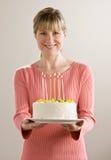 生日蛋糕对光检查暂挂被点燃的妇女 免版税图库摄影