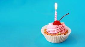 生日蛋糕用樱桃和灼烧的蜡烛为在蓝色背景的生日 股票录像