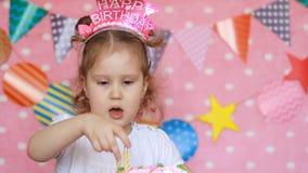 生日装饰品和装饰 逗人喜爱的小女孩装饰与蜡烛的一个欢乐蛋糕 的滑稽的愉快的孩子 股票录像