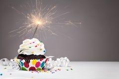 生日闪烁发光物杯形蛋糕 免版税库存图片