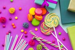 生日集合uncluding的贺卡、被包裹的礼物和甜点在紫红色的背景顶视图 图库摄影
