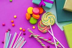 生日集合uncluding的贺卡、被包裹的礼物和甜点在紫红色的背景顶视图 免版税库存照片