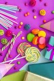 生日集合uncluding的贺卡、被包裹的礼物和甜点在紫红色的背景顶视图 库存图片
