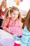 生日:生日女孩从朋友得到礼物 免版税图库摄影