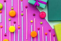 生日贺卡、被包裹的礼物和甜点在紫红色的背景顶视图 图库摄影
