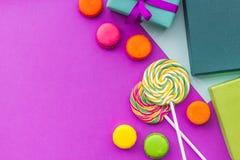 生日贺卡、被包裹的礼物和甜点在紫红色的背景顶视图copyspace 库存图片
