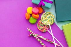 生日贺卡、被包裹的礼物和甜点在紫红色的背景顶视图copyspace 免版税库存照片