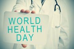 医生显示一块牌与文本世界卫生日 免版税库存照片
