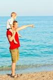 生显示某事给他的儿子在海 免版税图库摄影