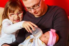 生有牛奶瓶的哺养的新出生的女婴 免版税库存照片