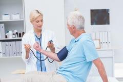 医生检查老人血压 免版税库存照片