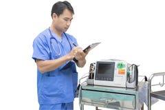 医生检查EKG显示器在急诊室 免版税库存照片