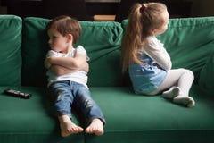 生气兄弟姐妹坐忽略的沙发在战斗以后 免版税库存图片