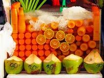 生气勃勃橙汁和椰子在街道与低价的果子或食物市场上购物 库存图片
