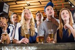 生气在酒吧柜台的爱好者观看的橄榄球 免版税库存照片
