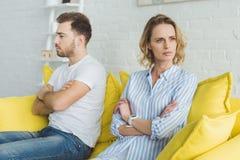生气夫妇以后坐黄色长沙发 库存图片