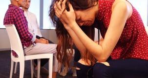 生气妇女坐与同事的椅子谈论在背景