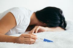 生气妇女谎言哀伤在与消极妊娠试验的床上 免版税图库摄影