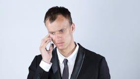 生气年轻商人谈话在智能手机 图库摄影