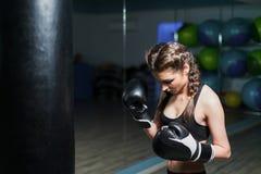 生气年轻在健身房敲打的战斗机拳击手女孩佩带的拳击手套 库存照片