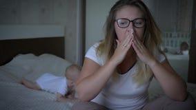 生气年轻妈咪在家坐床的边缘在爬行的婴孩背景的  股票视频