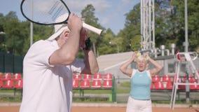 生气成熟夫妇丢失了在网球场的比赛 拿着头用手的老人和妇女 股票视频