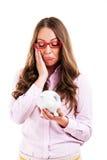 生气拿着存钱罐的妇女佩带的玻璃 免版税库存照片