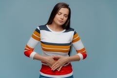 生气深色的夫人感到不适,遭受stomachache,感觉在腹部的难受,不满意表情,穿戴 库存图片