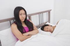 生气的妇女画象有睡觉在床上的人的 库存照片