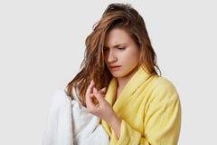 生气的年轻女人意识到她损坏了头发,注视着紧张末端,是湿的在洗澡以后,抹与白色 免版税库存图片