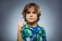 生气的恼怒的男孩与威胁在灰色背景隔绝的手指 库存照片