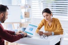 生气的疲乏的妇女感觉,当她的研究他的膝上型计算机时的同事 免版税库存图片