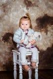 生气的白肤金发的小女孩坐白色椅子 免版税图库摄影