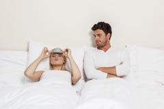 生气的年轻人在床上的看妇女佩带的眼罩 库存照片