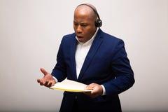 生气非裔美国人的商人谈话通过耳机 免版税库存图片