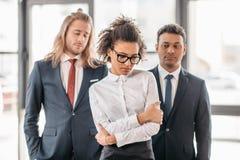 生气非裔美国人的站立在办公室的女实业家和两个商人 免版税库存图片