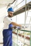 生气建筑工人工作成套装备的和一件防护盔甲的显示一个手指 在高脚手架的工作 库存图片