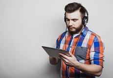 生活方式、人们和教育概念:通过在白色背景的耳机供以人员听audiobook 免版税库存照片