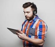 生活方式、人们和教育概念:通过在白色背景的耳机供以人员听audiobook 库存照片