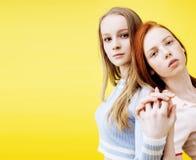 生活方式人概念:有两个相当年轻学校的十几岁的女孩乐趣愉快微笑在黄色背景特写镜头 免版税库存照片