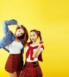 生活方式人概念:有两个相当年轻学校的十几岁的女孩乐趣愉快微笑在黄色背景 免版税库存照片