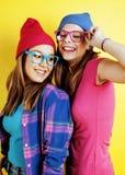 生活方式人概念:有两个相当年轻学校的十几岁的女孩乐趣愉快微笑在黄色背景 免版税库存图片